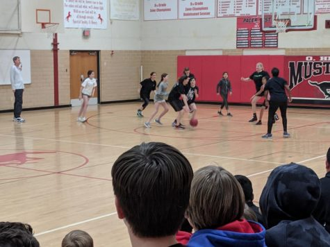 Coach McKey referees a student v. faculty basketball game.